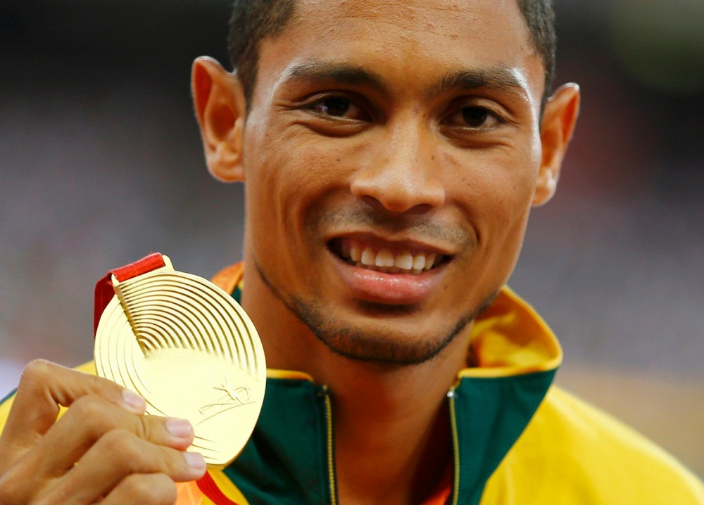 Wayde van Niekerk of South Africa presents his gold medal as he poses on the podium after the men's 400 metres final during the 15th IAAF World Championships at the National Stadium in Beijing